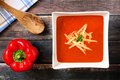 Red pepper soup in square bowl over wood Royalty Free Stock Photo