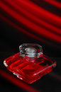 Red perfume bottle of parfume on a and black background with glasses Stock Photography