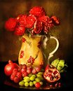 Red Petaled Flowers in White Red Floral Ceramic Vase Beside Red and Green Grapes