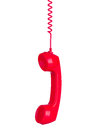 Red phone headset hanging by its wire isolated on white Royalty Free Stock Photo