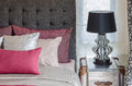 Red pillow on bed wirh lamp in bedroom Royalty Free Stock Photo