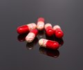 Red pills on black background Royalty Free Stock Photography
