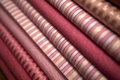 Red and pink luxury fabric textiles stack of folded woven textile fabrics in pinks reds with gold stripes Royalty Free Stock Photo