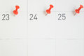 Red pins pinned on the dates of the month on calendar paper Royalty Free Stock Photo