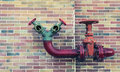 Red pipe line with brown valve on colorful brick wall Royalty Free Stock Photo