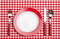 Red place setting in a restaurant with checkered table cloth Stock Images