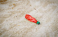 Red plastic bottle thrown on the beach Royalty Free Stock Photo