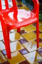 Red plastic garden chairs on the outdoor terrace in the home garden after the rain