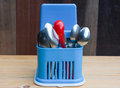 Red plastic spoon and stainless spoons in blue plastic storage Royalty Free Stock Photo