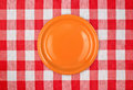 Red plate on checked tablecloth Royalty Free Stock Image