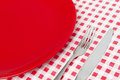 Red plate and cutlery on the chequered background Stock Images