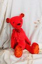 Red plush teddy bear sitting on a white embroidered fabric with floral lace Royalty Free Stock Photo