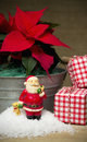 Red poinsettia flower still life in a zinc tub with three christmas present boxes and plastic santa figurine Stock Photo
