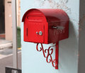 Red post box attached to wall Stock Images