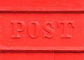 Red post box detail old english mailbox in the rain showing water drops and the word Stock Image