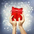 Red present box on christmas on shinning background womans hands holding up Stock Images
