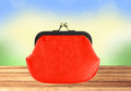 Red purse on wooden table over bright nature background Royalty Free Stock Photo