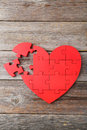 Red puzzle heart on grey wooden background Royalty Free Stock Photography