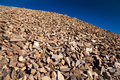 Red quartzite rocks talus slope mountain covered in reddish brown bright blue sky at high elevations Stock Photo