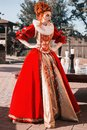 Red Queen in the castle. Red-haired woman in a chic vintage dress