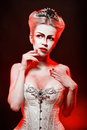 Red queen with a crown and a corset with make up in studio shot Stock Photo