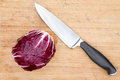 Red radicchio with a kitchen knife overhead view of single cleaned whole raw is displayed on an old bamboo cutting board Stock Photo