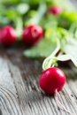 Red radish with leaves on wooden table Royalty Free Stock Photo