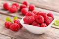 Red raspberries in bowl on grey wooden background Stock Photo