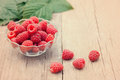 Red raspberries in bowl on wooden background. Toned effect Royalty Free Stock Photo