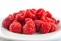 Red raspberries on white plate Royalty Free Stock Photo