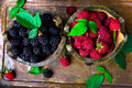 Red raspberry and  blackberry with leaf in a basket on vintage metal tray. Top view. Royalty Free Stock Photo