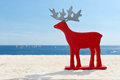 Red reindeer on vacation by the sea Royalty Free Stock Photo