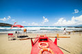 Red rescue boat, lifeguard station and girl walking with her dog on the beach Royalty Free Stock Photo