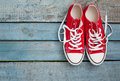 Red retro sneakers with loose braids on a blue wooden background Royalty Free Stock Photo