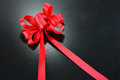 Red ribbon with bow on black background. Royalty Free Stock Photo