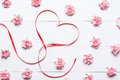Heart symbol on white wooden table with pink red and white roses