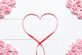 Pink red and white roses frame on white wooden background with e