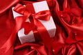 Red ribbon holiday gift on satin Royalty Free Stock Images
