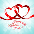 Red ribbon with two hearts intertwined in a shape of Royalty Free Stock Images