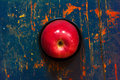 Red ripe apple in a black saucer on old background cracked board with spots closeup top view Royalty Free Stock Photos