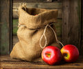 Red ripe apples in a bag on wooden background Stock Photos