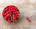 Red ripe cherries with tails in a circular plate on the old wooden background Royalty Free Stock Photo
