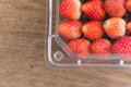Red ripe strawberry in plastic box of packaging on wood Royalty Free Stock Photo