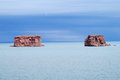 Red rock formations in the blue lake water Royalty Free Stock Photo