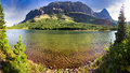 Red rock lake panorama rocks pine trees and clear green colored water at in glacier national park montana Stock Image