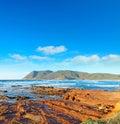 Red rocks by the shore in porto ferro sardinia Stock Images