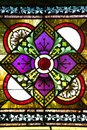 Red rose centered in stained glass window square and half circle patterns set a church that features green purple yellow Stock Photo
