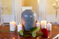 Red rose and cremation urn with burning candles Royalty Free Stock Photo