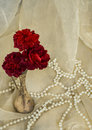 Red roses in an antique silver vase with pearls on cream colored fabric Stock Photos