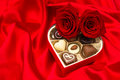 Red roses and assorted chocolate pralines in gift box golden heart shaped on satin background Royalty Free Stock Images